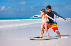 Father and daughter practicing surfing. Father and daughter at beach practicing surfing position Royalty Free Stock Photo