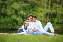 Father of a daughter and a pregnant mom at a picnic. Royalty Free Stock Photography