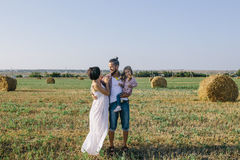 Father, daughter and pregnant mother enjoying life outdoor in field Royalty Free Stock Photos