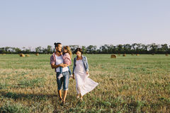 Father, daughter and pregnant mother enjoying life outdoor in field Stock Images
