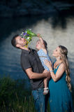 Father, daughter and pregnant mother having fun outdoors Stock Photos
