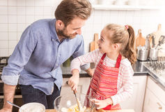 Father and daughter preparing cookie dough in the kitchen Stock Images