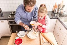 Father and daughter preparing cookie dough in the kitchen Royalty Free Stock Photography
