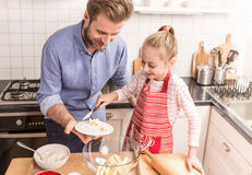 Father and daughter preparing cookie dough in the kitchen Royalty Free Stock Images