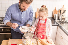 Father and daughter preparing cookie dough in the kitchen Stock Photos