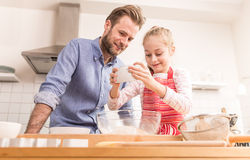 Father and daughter preparing cookie dough in the kitchen Royalty Free Stock Image