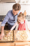 Father and daughter preparing cookies to bake in the kitchen Stock Photography
