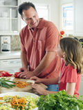 Father and daughter (8-10) preparing food on kitchen worktop, man chopping tomatoes, smiling, side view Stock Photo