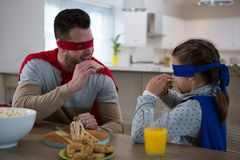 Father and daughter pretending to be superhero. While having breakfast Stock Photos