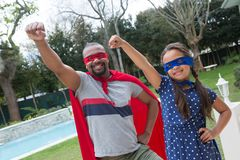 Father and daughter pretending to be a superhero. Smiling father and daughter pretending to be a superhero Royalty Free Stock Images