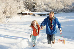 Father And Daughter Pulling Sledge Up Snowy Hill Stock Image