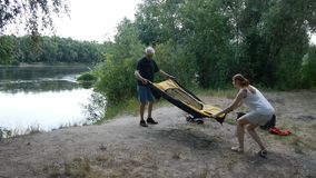 Father and daughter putting up tent, preparing to overnight in wild, green tourism, hiking. Happy travels concept. Father and daughter putting up tent stock footage