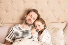 Father and daughter in pyjamas hugging in a bed. Smiling caucasian father and daughter in pyjamas hugging in a bed. Morning in a bedroom - happy family time Royalty Free Stock Image