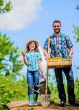 Father and daughter on rancho. summer farming. farmer man with little girl. garden tools, shovel and watering can. kid