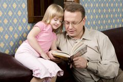 Father and daughter are readin. G a book sitting on the sofa Royalty Free Stock Photo