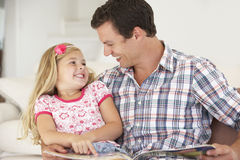 Father And Daughter Reading Book In Bedroom Stock Photo