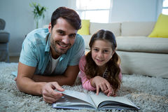 Father and daughter reading book in the living room Royalty Free Stock Images