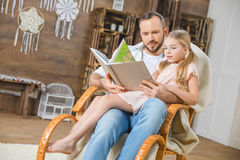 Father and daughter reading book. Father and daughter sitting together in rocking chair and reading book Stock Photos