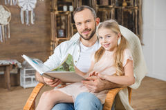 Father and daughter reading book. Together and smiling at camera Stock Images