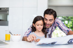 Father and daughter reading newspaper at home Stock Photos