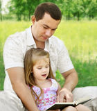 Father with daughter reading in the park Royalty Free Stock Photo