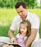 Father with daughter reading in the park Royalty Free Stock Photography