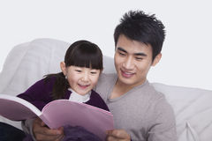Father and daughter reading on the sofa Royalty Free Stock Photos