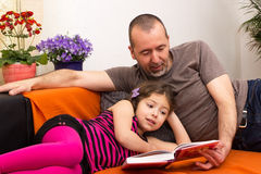 Father and daughter reading together Stock Images