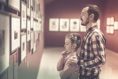 Father and daughter regarding exhibition of photos in the museum Stock Image