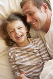 Father And Daughter Relaxing In Bed Stock Photos