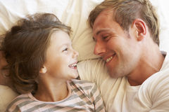 Father And Daughter Relaxing In Bed Stock Image