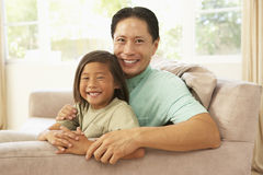 Father And Daughter Relaxing At Home Stock Photo