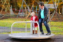 Father and daughter relaxing at playground Stock Image