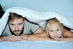 Father And Daughter Relaxing Together In Bed. Looking at camera Stock Photography