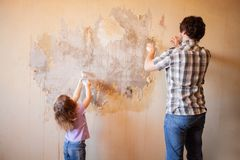 Father and daughter repairing wall, holding putty knife stock photo
