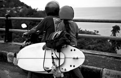 Father with the daughter ride by motorcycle with surfing boards to the beach. Black-white photo. Stock Images