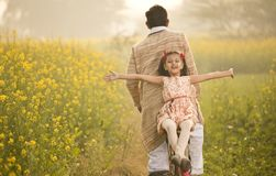 Father with daughter riding bicycle on agriculture field. Happy farmer with his daughter riding bicycle on rapeseed agriculture field stock images