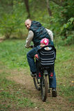 Father and daughter riding bike in the forest Royalty Free Stock Image