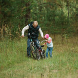 Father and daughter riding bike in the forest Stock Photo