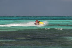 Father and daughter riding a jet ski. Stock Photography