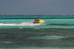 Father and daughter riding a jet ski. Father and daughter riding a jet ski in colorful green water, Bahamas Royalty Free Stock Image