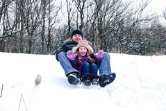 Father and daughter riding on a sledge Stock Photography