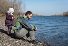 Father and daughter on a river bank Stock Image