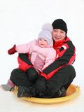 Father with daughter rolling on snow saucer Royalty Free Stock Photography