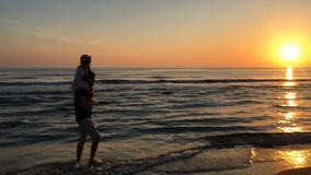 Father and daughter run along the beach at sunset. stock video footage