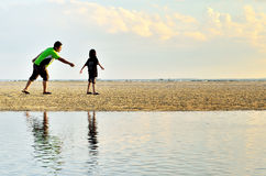 A father and daughter running along the beach Stock Photography