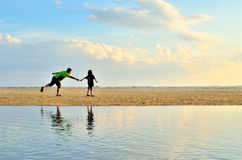 A father and daughter running along the beach Stock Photo