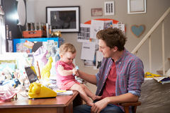Father With Daughter Running Small Business From Home Office Stock Images
