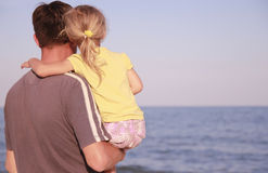 Father and daughter on the sea shore Stock Photos