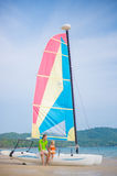 Father and daughter seat on side of catamaran sail boat on ocean Stock Photos